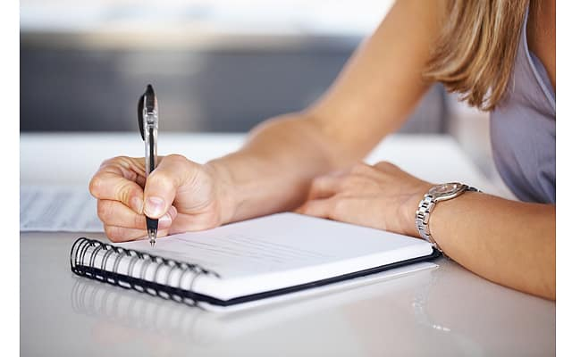 Cropped image of woman's hand with pen writing down notes